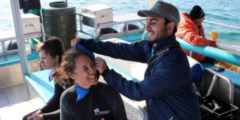 Zuid-Afrika-MArine-Conservation-Gansbaai-Assisting-clients-with-wetsuits